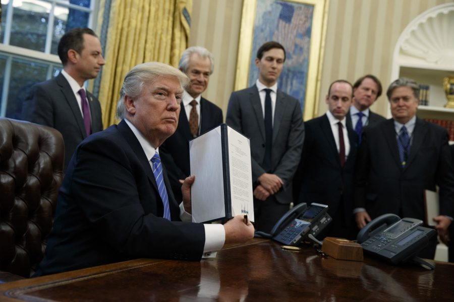 Trump signing the executive order on Monday, January 23.