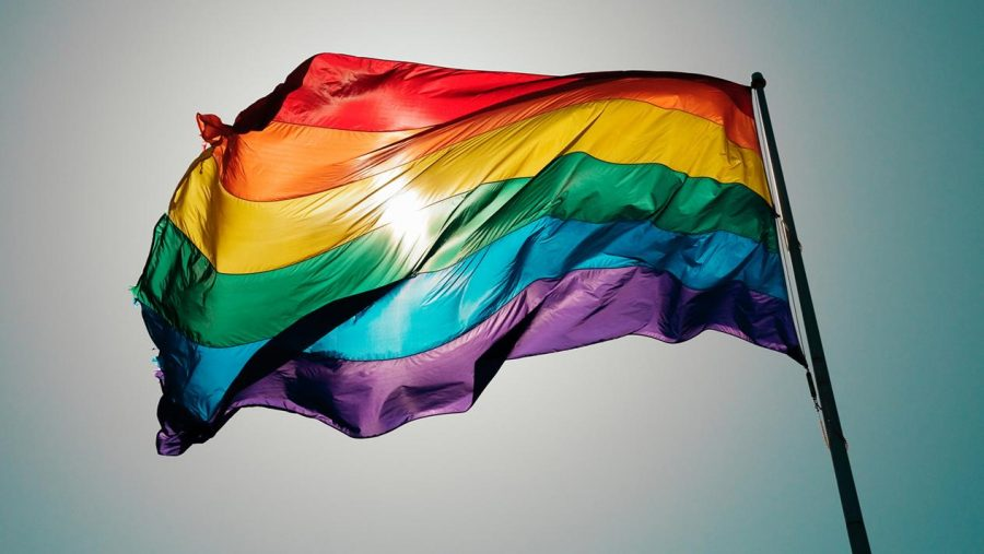 The gay pride flag waves in the sky.