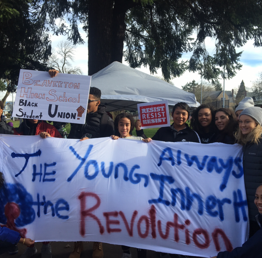 """Students from Beaverton's Black Student Union carry a banner saying, """"The Young Always Inherit the Revolution."""""""