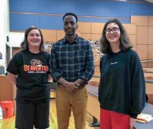 Hummer reporters Beatrice and Eleanor Kahn stand with author Abdi Nor Iftin in the MD Lecture Hall.