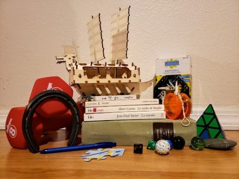 An assortment of fun objects sits on the floor in front of a wall.