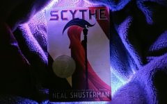 A copy of Scythe enjoys a luxurious existence upon a fluffy blanket, surrounded by lights.
