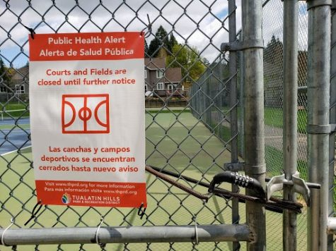 The tennis courts at Mitchell Park are locked with a notice nearby notifying community members of the closure.