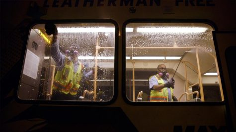 Two TriMet employees sanitize a vehicle at night.