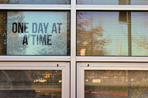 A reflective window at BHS displays a motivational poster.
