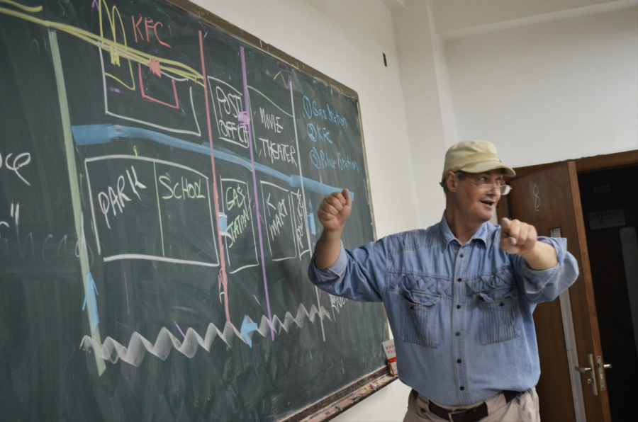 A teacher draws a map on a chalkboard.