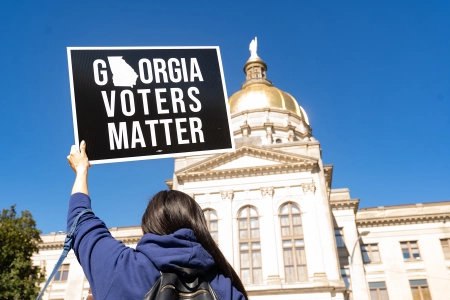 A protester holds up a sign in front of the Georgia capitol building. A recently passed bill has drawn mixed reactions, with proponents saying it makes it easier to vote and critics saying the opposite.