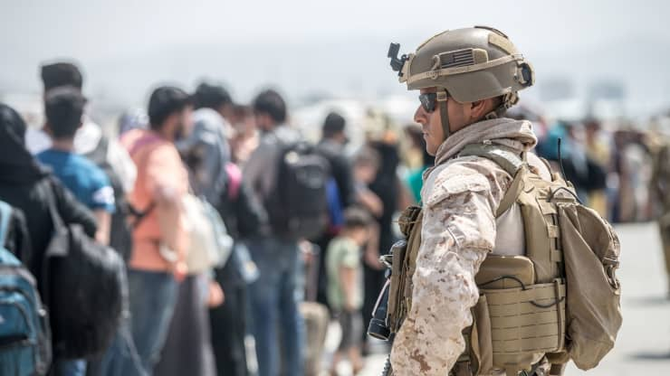 Afghan refugees head toward an evacuation point as a US Marine looks on