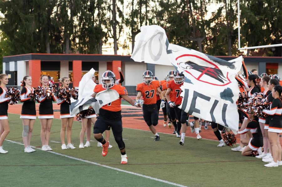 The football team charges through the cheerleaders poster, which reads No Fly Zone!! in reference to the Southridge Skyhawks.